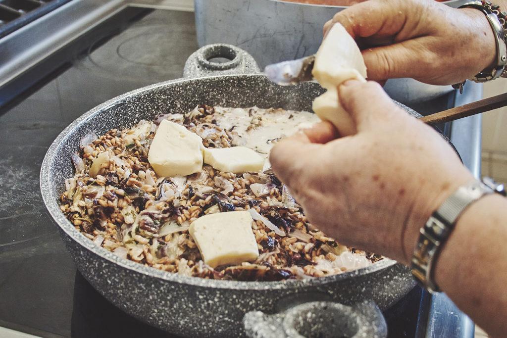 mani che aggiungono burro alla padella con farro e radicchio